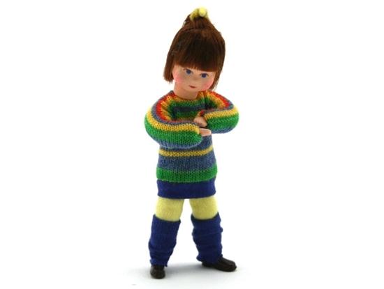 Meisje poppenhuis pop met bruin haar. Ze draagt een lange groen gestreepte trui.