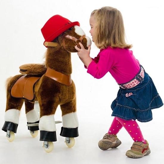 Petit cheval en pluche brun sur roulettes que l'on peut monter.  Il porte un chapeau rouge. Une petite fille lui tient la tête et lui sourit.