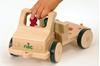 Camion en bois, modèle de base court, pour placer différents outils. Une main placée sur le guidon conduit le camion.