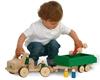 Un petit garçon joue avec un camion en bois, modèle de base long auquel est attaché une remoque verte.