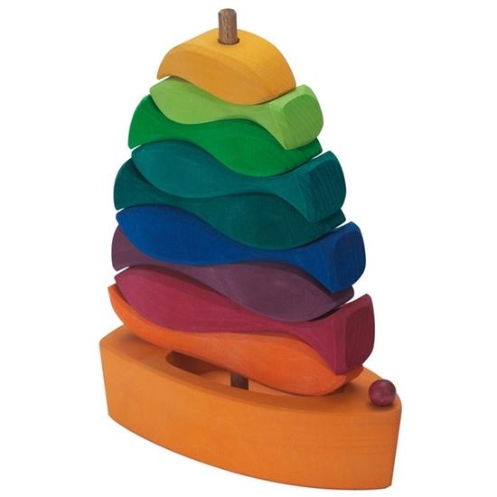 Een oranje houten boot met op de mast ervan 9 houten visjes gestapeld van beneden tot boven in afnemende grootte en in verschillende kleuren. Van onder tot boven 1 oranje, 1 bordeaux, 1 paarse, 1 blauwe, 1 donkergroene, 1 groene, 1 lichtgroene en 1 gele.
