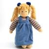Pop in bio katoen en wol met blauwe ogen en 2 blonde staartjes. Ze staat recht en draagt een gestreepte T-shirt met lange mouwen en een blauwe overal jurk.