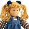 Close up sur le visage d'une poupée de chiffon aux yeux bleus et aux cheveux blonds portant un sweat rayé et une robe de velours bleu.