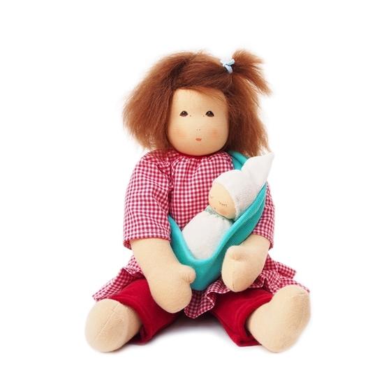 Voddenpop met bruin mohair haar en bruine ogen. Ze draagt een rode lange broek en een rood geruite bloes met driekwart mouwen. Om haar hals en rug draagt ze een groene draagzak waar haar baby in ligt te slapen.