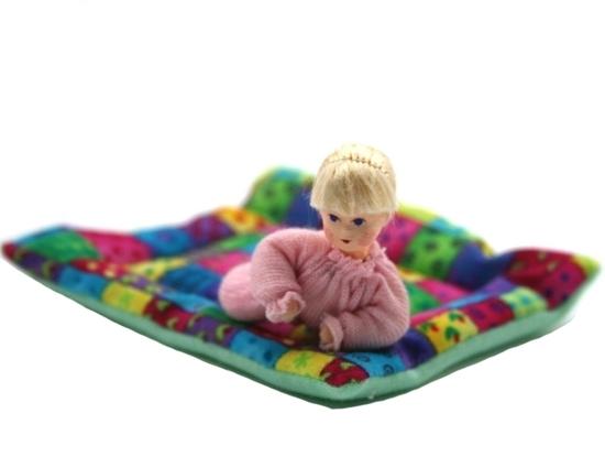 Een blond baby popje met roos kruippakje ligt op een veelkleurig patchwork deken.