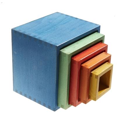 5 houten kubussen van verschillende maten en kleuren, die allemaal in elkaar passen. De grootste is blauw, de kleinste geel met daartussen 1 groene, 1 rode, en 1 oranje.
