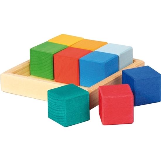 Een natuurhouten vierkant houten schaaltje met daarin 6 kleurige houten kubussen, 1 lichtblauwe, 1 blauwe, 1 oranje, 1 groene, 1 lichtgele en een donkergele. Naast het schaaltje liggen nog 3 kubussen, 1 blauwgroene, 1 rode en 1 donkerblauwe.