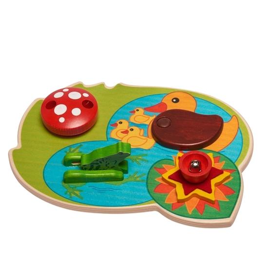 Groene houten plaat met een blauwe vijver op getekend waar een gele moeder eend en 3 baby eendjes op zwemmen, met een groene kikker, een rode paddestoel en een rode waterlelie, allemaal activiteiten speeltjes voor baby's.