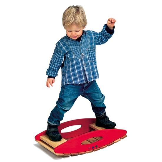 Un enfant blond, habillé tout de bleu, se tient en équilibre sur une balançoire en bois d'aulne massif couleur rouge et bois naturel.