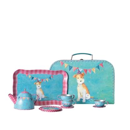 Een klein blauw valiesje met afbeelding van de hond Eliott staat recht. Ertegen aangeleund staat een blauw dienblad in blik met roze boord en afbeelding van dezelfde hond. Voor het dienblad staat van links naar rechts een bolle theepot, een stapeltje van 4 dessertborden, 3 gestapelde kopjes en schoteltjes en een kopje en schoteltje apart, allemaal in blauw en roos blik.