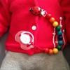 Le ventre d'un bébé au pull rouge auquel est attaché la chaîne à sucette aux perles de bois multicolores.