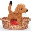 Dans un panier en osier pour chien se trouve debout un petit chien en peluche brun, debout sur le coussin à carreaux rouges et blancs qui garnit le panier.